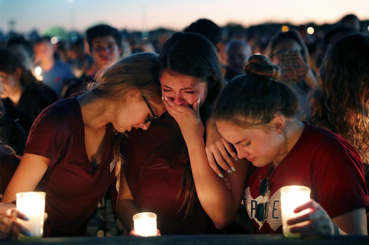 Image: Students console each other during a candlelight vigil for the victims of the shooting at Marjory Stoneman Douglas High School