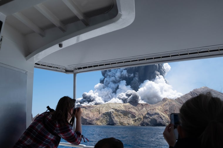 Tourists take pictures of the volcanic eruption on White Island from a boat shuttling people to safety.