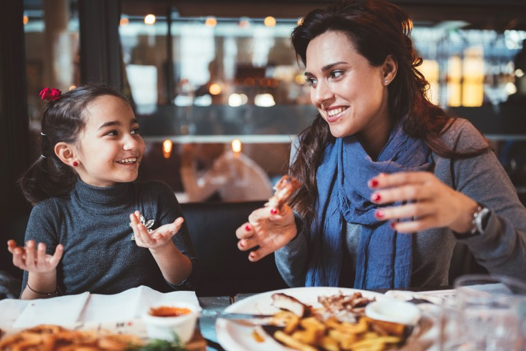 Image: Mother with little daughter eating dinner in restaurant