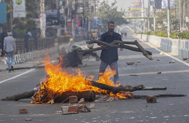 Image: A protester sets fire to block traffic in Gauhati, India