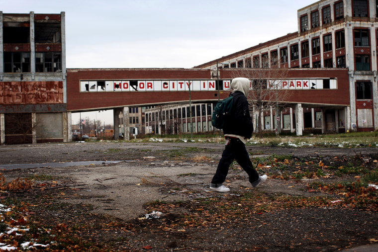 Image: A man walks past the former Packard Motor Car Company building in Detroit in 2008.