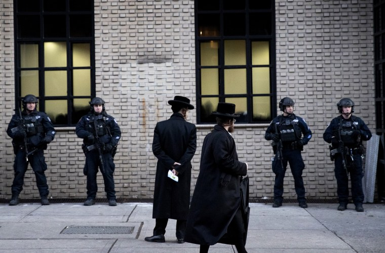 Image: Jewish men pass police guarding the funeral for Mosche Deutsch, who was killed in a Jersey City shooting at a kosher market on Tuesday, in Brooklyn on Dec. 11, 2019.