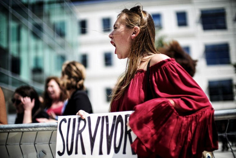 Image: Meghan Downey protests as Education Secretary Betsy DeVos announces changes in federal policy for investigating reports of sexual assault on college campuses in Arlington, Va., on Sept. 7, 2017.