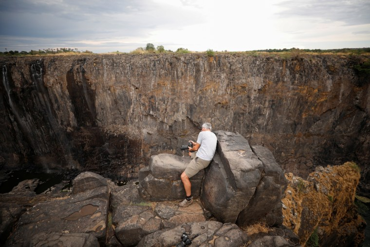 Image: Visitors take pictures before dry cliffs following a prolonged drought at Victoria Falls