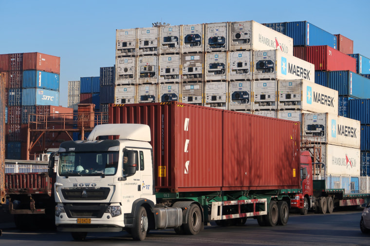 Image: Worker drives a truck carrying a container at a logistics center near Tianjin port