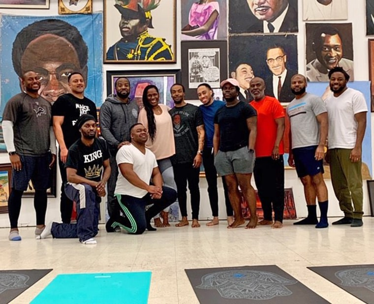 """Sherri Doucette, Founder, Litehouse Wellness, stands with attendees of """"Broga - Yoga for the Brothers"""" class at the Pan African Connection in South Dallas."""