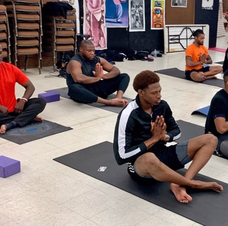 """Men in a seated pose in Sherri Doucette's """"Broga - Yoga for the Brothers"""" class at the Pan African Connection in South Dallas."""