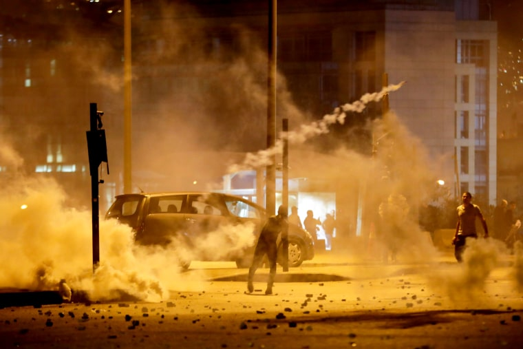 Image: Demonstrators hurl tear-gas canisters back at riot police in Beirut, Lebanon, on Dec. 14, 2019.