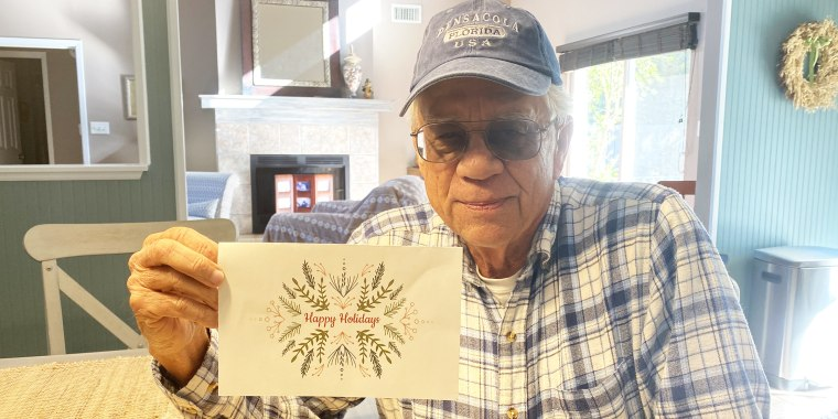 Mike Esmond poses with his copy of the card sent to families this month to let them know he'd paid off their utility bills.