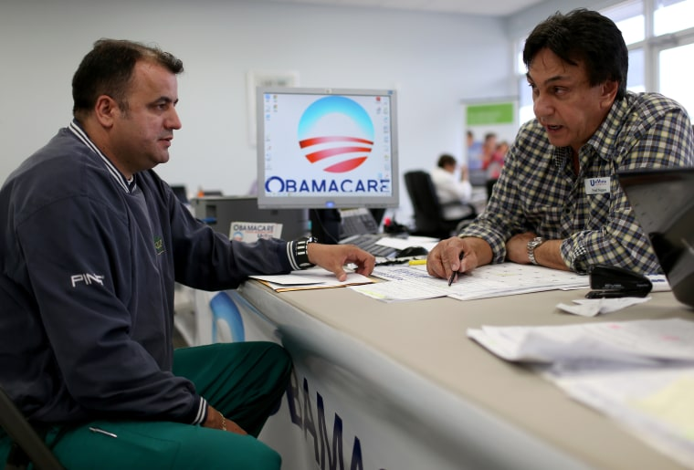 Image: Ariel Fernandez, left, sits with Noel Nogues, an insurance adviser, as he signs up for the Affordable Care Act in Florida in 2015.