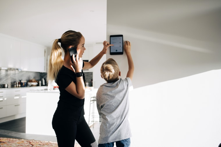 Teenage girl talking on phone using digital tablet by brother standing at home