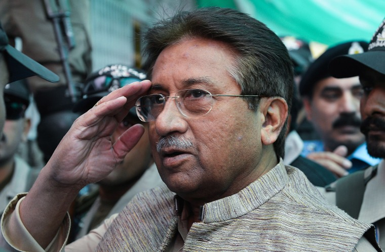 Image: Former Pakistani president Pervez Musharraf is escorted by soldiers as he salutes on his arrival at an anti-terrorism court in Islamabad.
