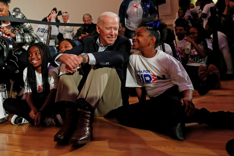 Former Vice President Joe Biden sits with kids from the Union Baptist Crusaders drill team during an event in Waterloo, Iowa, on Dec. 5, 2019.