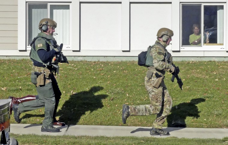 Police officers run past the Babcock Village apartments on Dec. 19, 2019, in Westerly, R.I.
