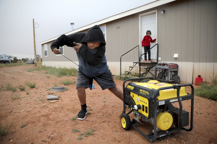 Jayden Long, 13, starts the generator behind his home on the Navajo Reservation in Arizona so that he can charge his cell phone inside the family home on May 8, 2019.