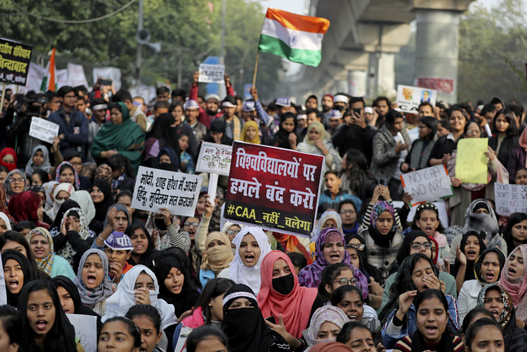 """Indian students of the Jamia Millia Islamia University and locals participate in a protest demonstration against a new citizenship law in New Delhi, India, Saturday. Critics say the law violates India's secular constitution and call it the latest effort by the Narendra Modi government to marginalize the country's 200 million Muslims. Modi has defended the law as a humanitarian gesture. Placard center reads """"Stop attacking universities."""""""