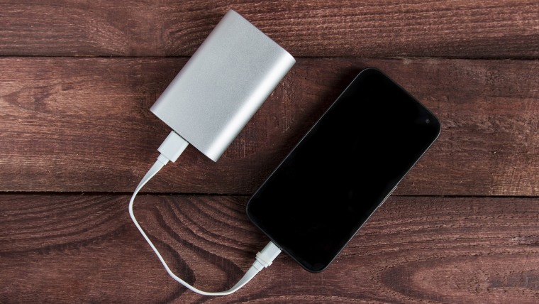 Charging smartphone with grey portable external battery on wooden Desk .; Shutterstock ID 640821112; Purchase Order: -