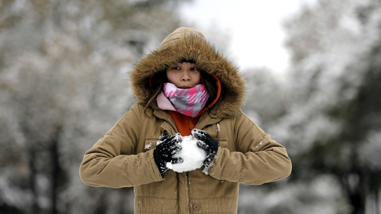 Image: A woman makes a snowball while playing in Spring, Texas, on Dec. 8, 2017.