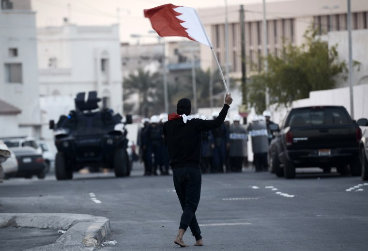 A protester holds a Bahraini flag in front of riot police during clashes after a protest against the arrest of the head of the banned Shiite opposition movement, Sheikh Ali Salman, on Dec. 29, 2014, in Manama.
