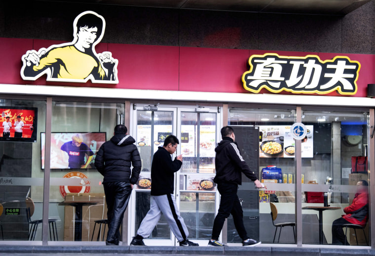 Image: People walk past the restaurant Real Kung Fu, or Zhen Gongfu in Mandarin, run by fast food chain Kungfu Catering Management, in Beijing