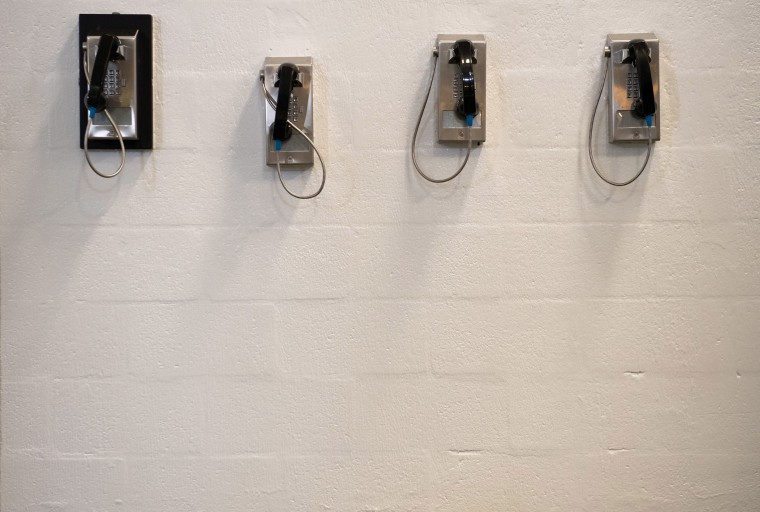 Image: A bank of telephones for use by detainees is seen inside the Caroline Detention Facility in Bowling Green, Virginia.