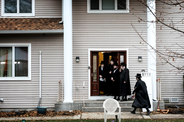 Image: People gather at the residence of a rabbi where five people were stabbed during a Hannukah celebration in Monsey, N.Y., on Dec. 29, 2019.