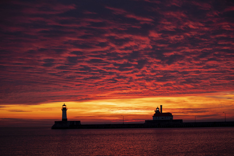 The first sunrise of 2020 brings deep orange and pink colors over the Duluth Harbor North and South Breakwater Lighthouses in Duluth, Minn., Wednesday, Jan. 1, 2020.