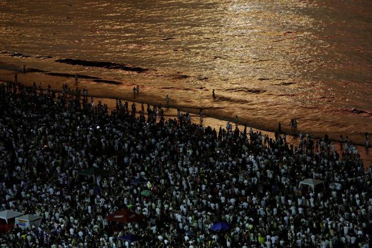 Image: People watch as fireworks explode over Copacabana beach during New Year celebrations in Rio de Janeiro