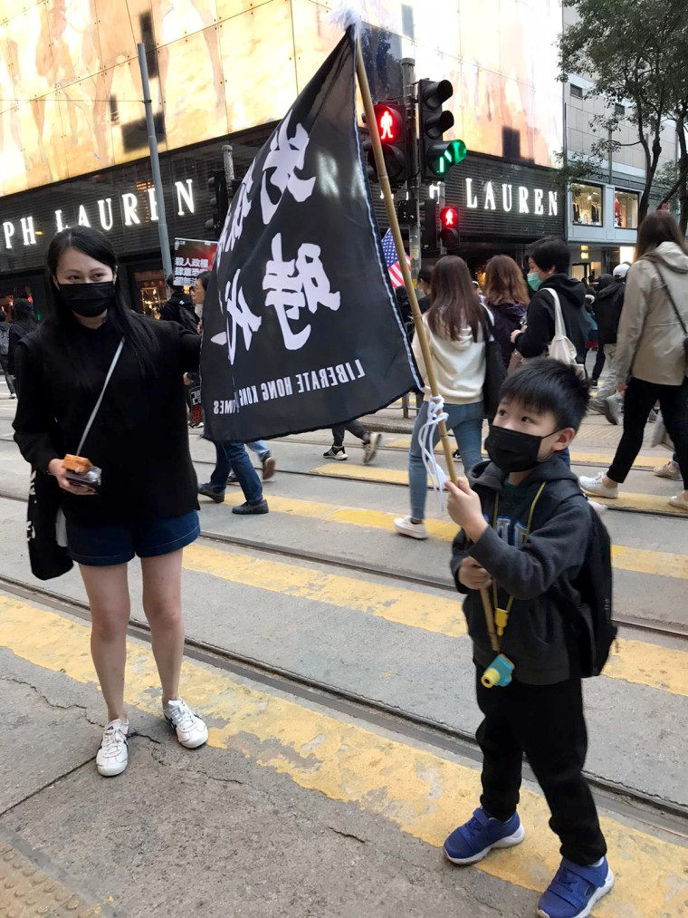 """Image: Sandy Lo attended the rally with her young son. Their banner says, """"liberate Hong Kong, revolution of our time."""""""