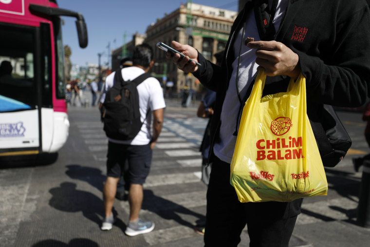 Image: A pedestrian carries a plastic bag after a ban on plastic bags took effect in Mexico City on Jan. 1, 2020.