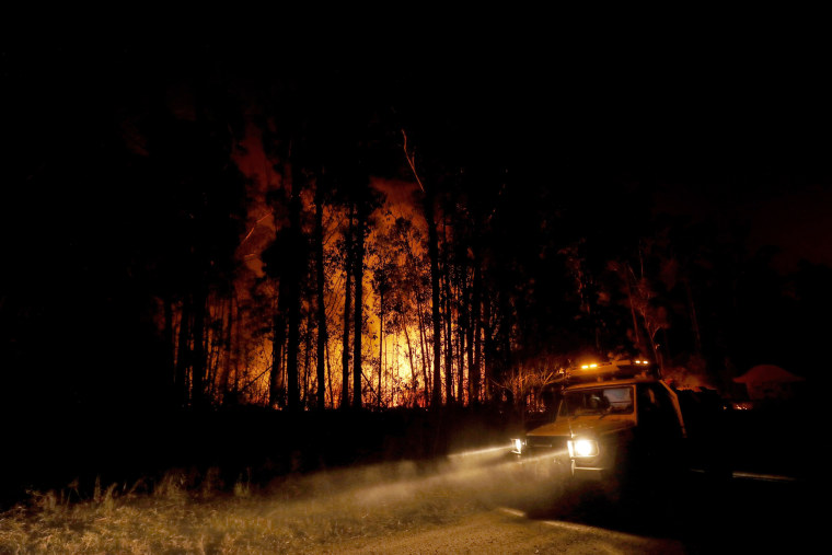 Image: Emergency crews monitor a fire burning between the towns of Orbost and Lakes Entrance near Mallacoota, Australia, on Jan. 2, 2020.