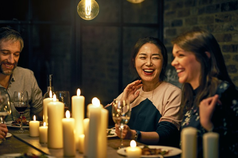 Two female friends sitting next to each other and laughing during meal