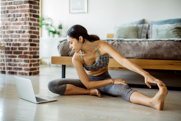 Image: Young women practicing yoga in bedroom. She looking video lesson of yoga on laptop and exercising