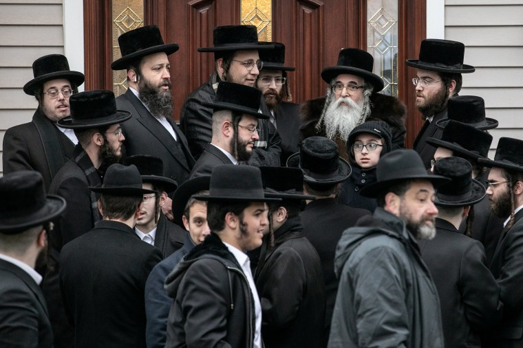 Image: Rabbi Chaim Rottenberg stands with people in front of his residence in Monsey