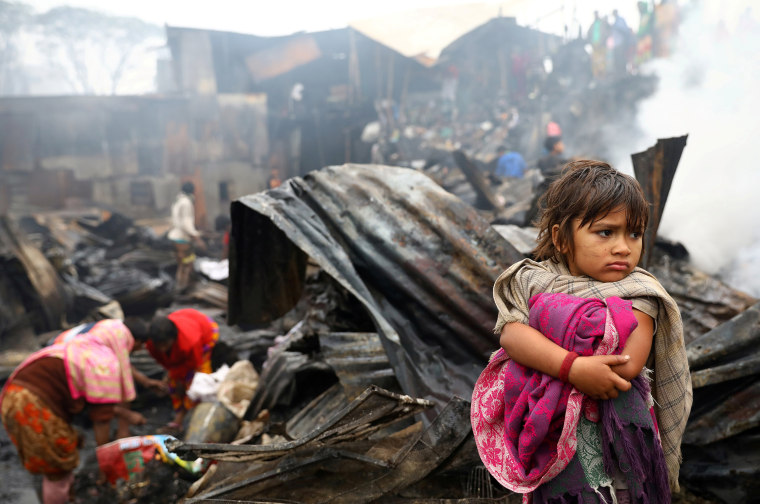 Image: Child looks on, whose shelter has been burned after a fire broke out in a slum in Dhaka