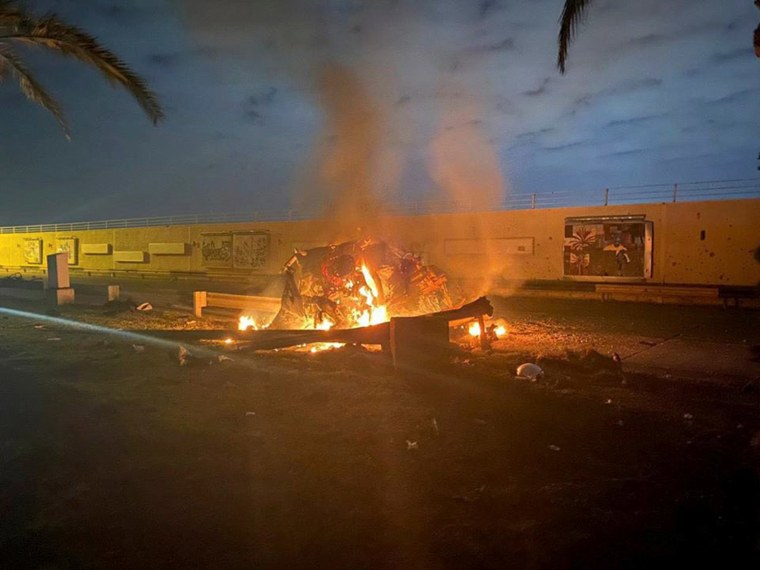 Image: Burning debris are seen on a road near Baghdad International Airport
