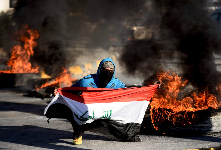 Image: An Iraqi demonstrator carries a flag during a protest over airstrikes that killed top Iranian and Iraqi military commanders in Najaf on Jan. 5, 2020.