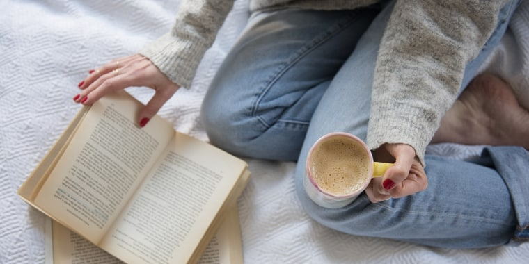 Woman in bed with coffee and book