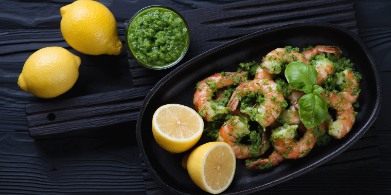 Tiger shrimps with parsley sauce and lemon, black wooden surface, top view; Shutterstock ID 566389513; Purchase Order: -; Segment/Job: -; Client/Licensee: -