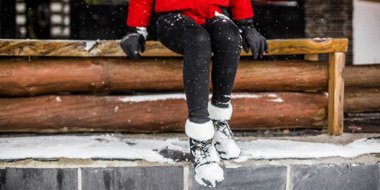 low section woman with boots covered in snow