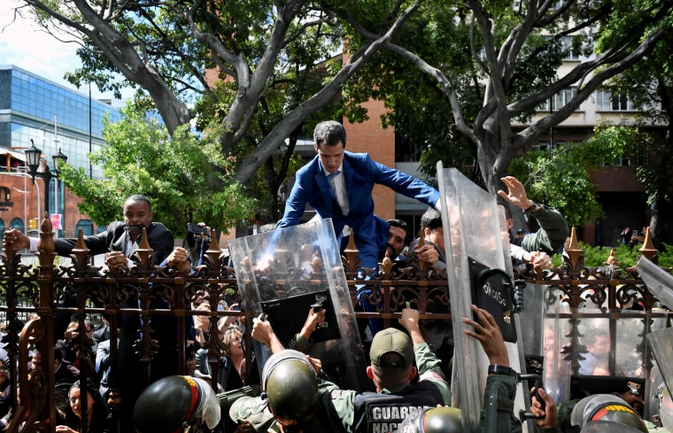 Image: Venezuelan opposition leader Juan Guaido climbs a fence to reach the National Assembly building in Caracas on Jan. 5, 2020.