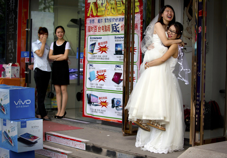 Image: Li Tingting, second from right, laughs as she is lifted off the ground by her wife Teresa Xu, right, outside of a beauty salon where the two were preparing for their wedding as clerks from an adjacent shop look on in Beijing