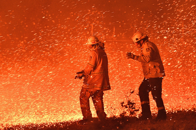 Firefighters struggle against the strong wind in an effort to secure nearby houses from bushfires