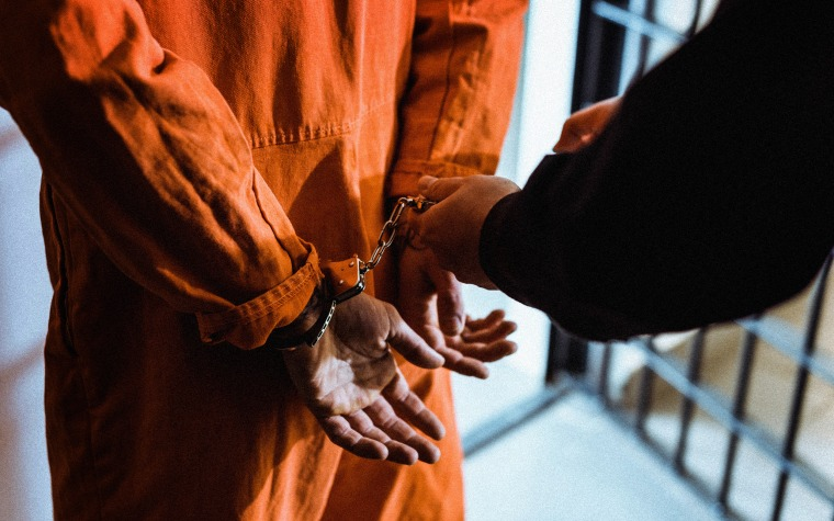 Image: Prisoner with handcuffs in cell