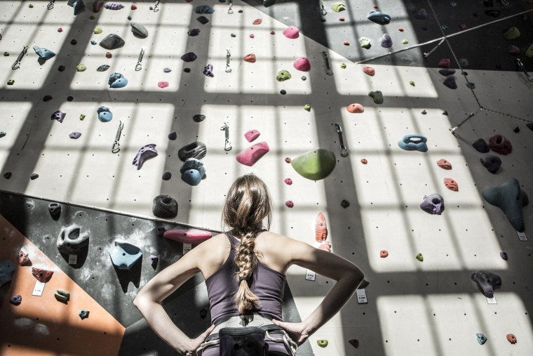 Image: Athlete examining rock wall in gym