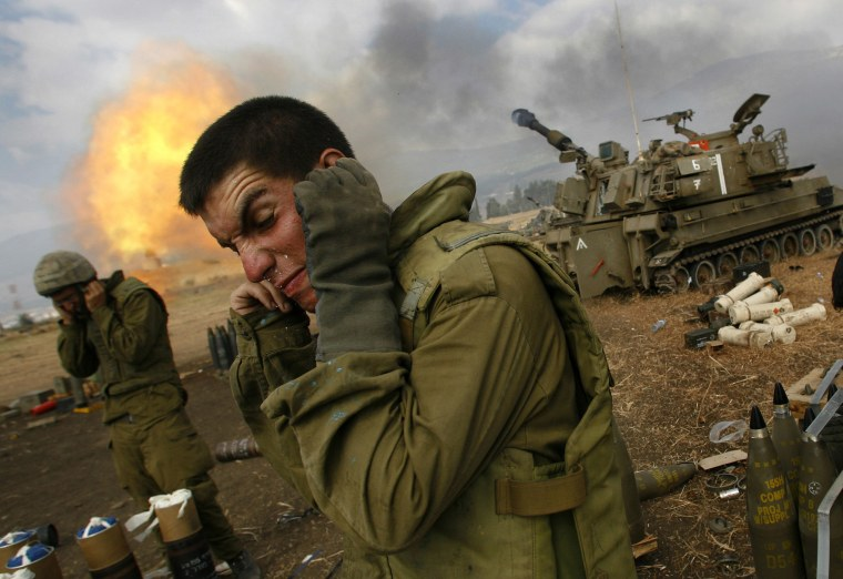 Image: Israeli soldiers cover their ears as an artillery unit fires shells towards southern Lebanon from a position near Kiryat Shmona in northern Israel, near the border with Lebanon