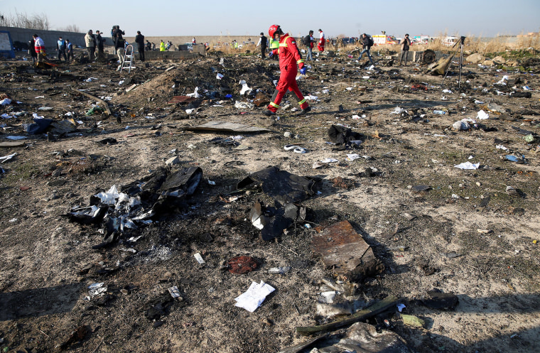 Image: A member of a rescue team walks among debris from a plane belonging to Ukraine International Airlines, that crashed after a take-off from Iran's Imam Khomeini airport, on the outskirts of Tehran