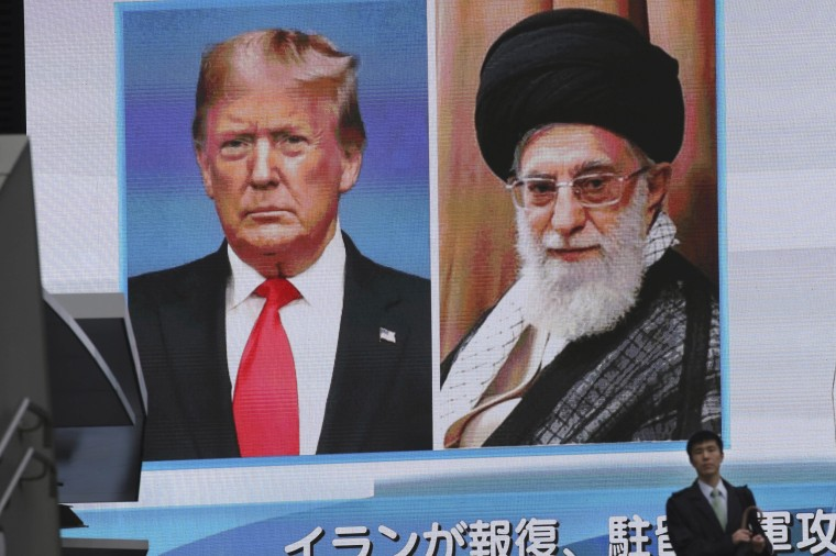 Image: A man walks by a huge screen showing U.S. President Donald Trump, left, and Iranian Supreme Leader Ayatollah Ali Khamenei, in Tokyo