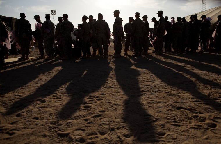 Image: Soldiers wait to pack their weapons at Camp Virginia in Kuwait after departing Iraq to return to the United States on Dec. 19, 2011.