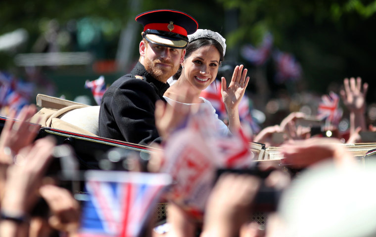 Image: Prince Harry and Meghan, Duchess of Sussex, wave from their carriage during a procession after their wedding ceremony in Windsor on May 19, 2018.